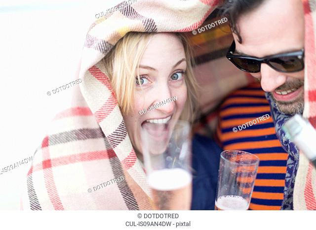 Couple drinking wine and laughing under blanket