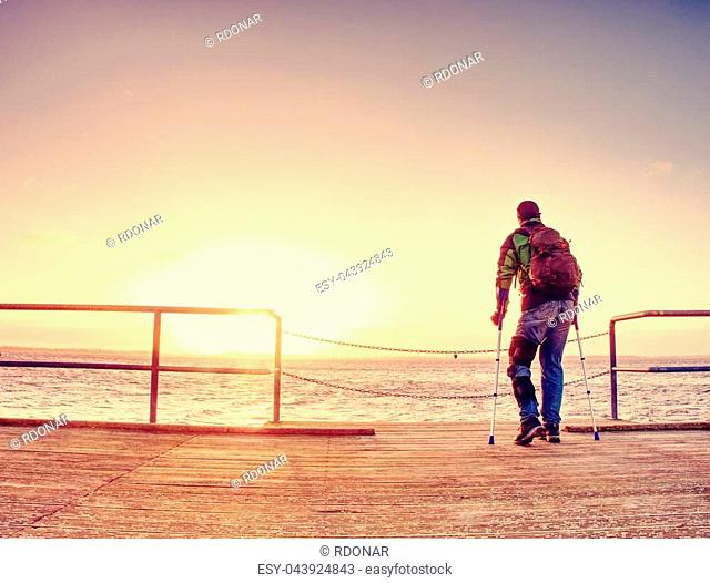 Silhouette of man with backpack on the wooden pier on the calm sea bay with sun at horizon. Beautiful golden sunset