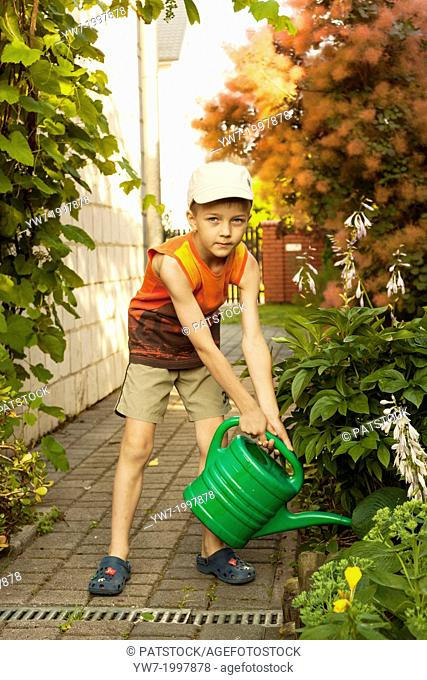 Boy watering flowers with plastic green water can in a garden