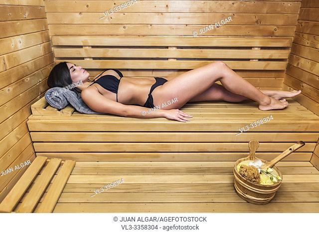 Young brunette lying alone on wooden shelf in steam room and relaxing