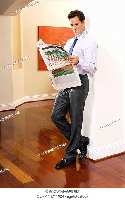 Businessman reading a newspaper in a house