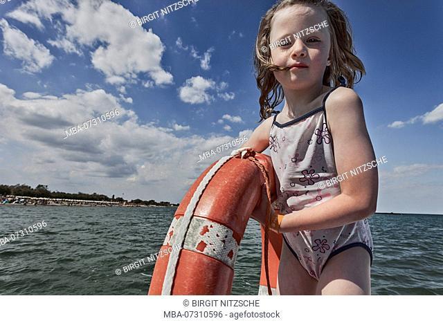 Girl on boat holds lifebuoy