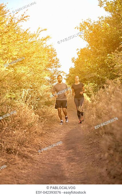 Young couple jogging down a mountainpath in the late afternoon sunshine with trees behind, while wearing casual clothing