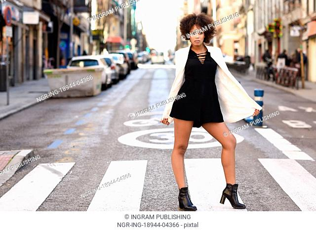 Young black woman with afro hairstyle walking on a crosswalk in an urban street. Mixed girl wearing white jacket and black dress with city background