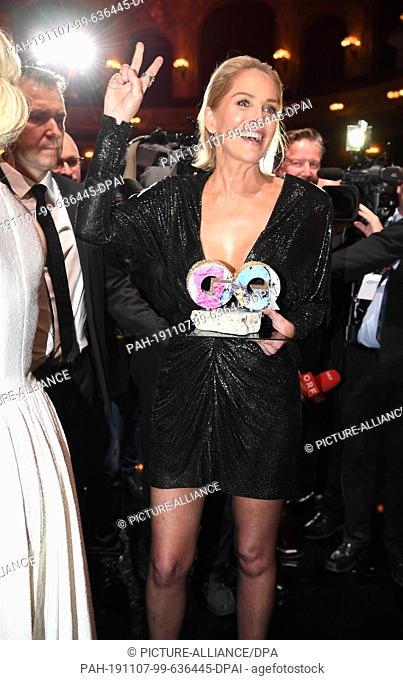 07 November 2019, Berlin: US actress Sharon Stone makes a Vicory Mark while holding the Woman of the Year Award in her hand at the 2019 GQ Men of the Year...
