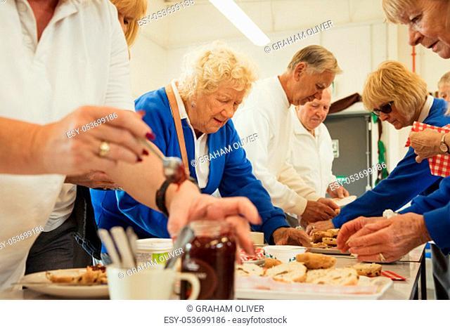 Senior friends taking a break and having some jam scones