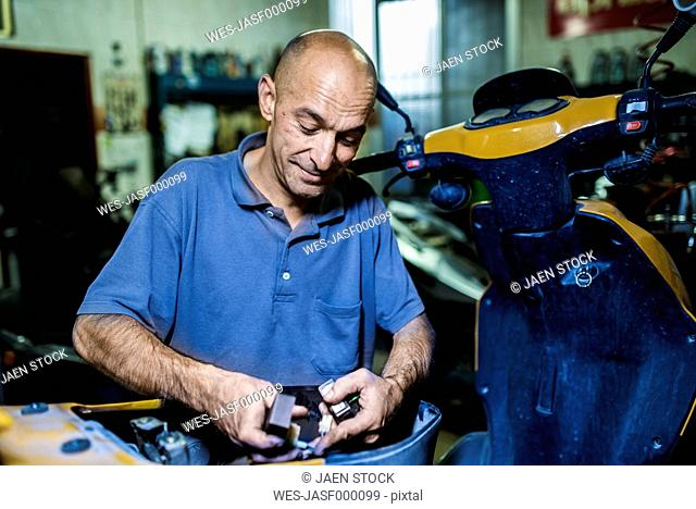 Mechanic working in his motor scooter workshop
