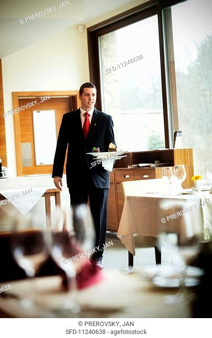 A waiter carrying two plates in a restaurant