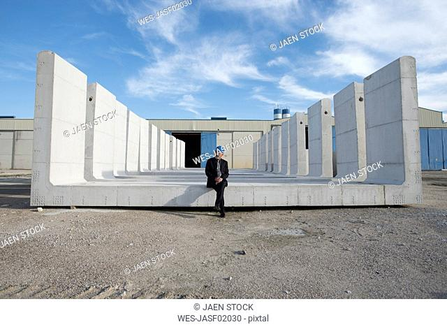 Businessman sitting on concrete block on industrial site
