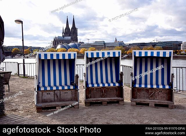 26 October 2020, North Rhine-Westphalia, Cologne: Strandkörbe are located on the Rheinterrassen in front of the Rhine and Cologne Cathedral