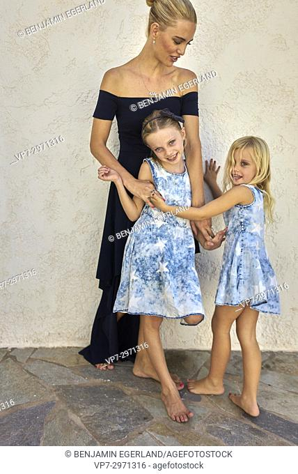 candid family, mother with two daughters enjoying togetherness in front of house wall. Australian ethnicity