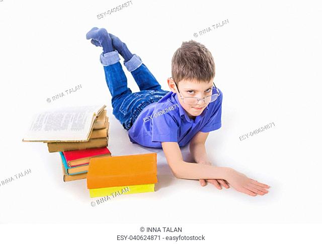 Portrait of cute teen schoolboy sitting near books and typing on laptop keyboard. Happy and surprised little boy, caucasian model isolated on white studio...