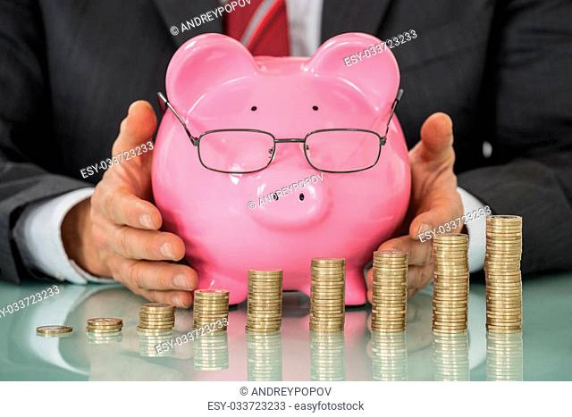 Close-up Of Businessman Hand Covering Piggy Bank With Stacked Coins At Desk