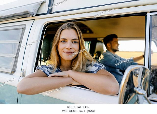 Portrait of smiling woman leaning out of window of a camper van with man driving