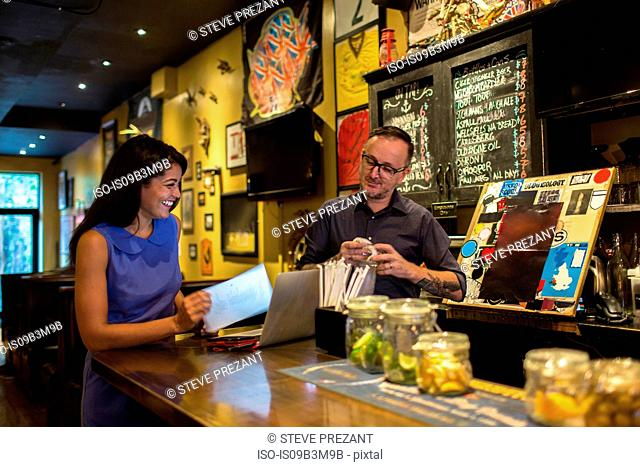 Barman laughing with female customer at public house counter