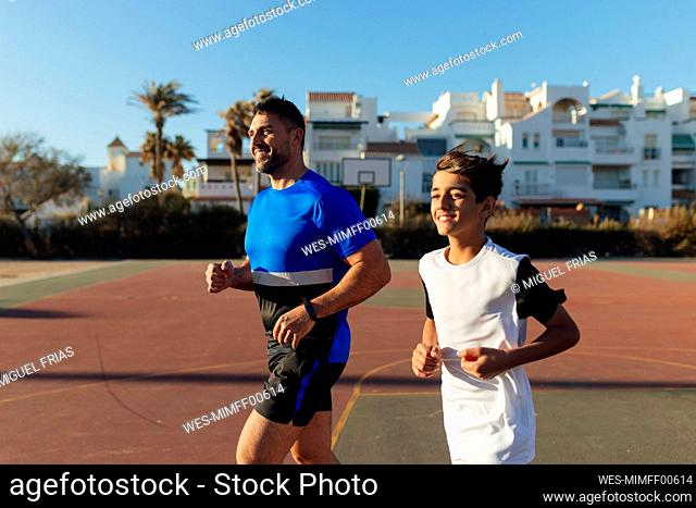 Smiling father and son looking away while running on sports court
