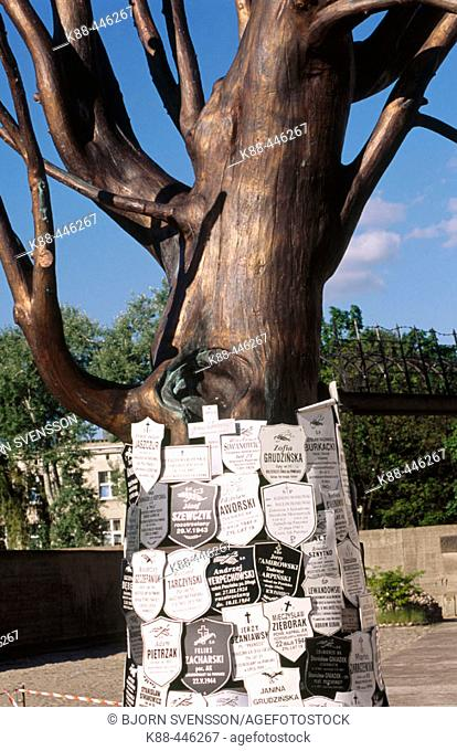 Obituaries cover a tree at the former entrance to Pawiak prison. Warsaw. Poland