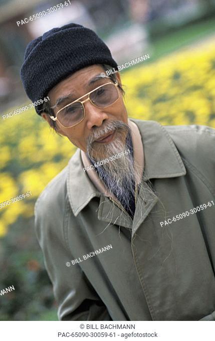 Vietnam, Hanoi, Portrait of local elderly man with white beard, yellow flowers in background