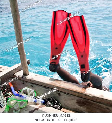 Low section of diver wearing flippers jumping off boat