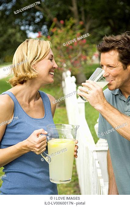 couple in garden with jug of lemonade