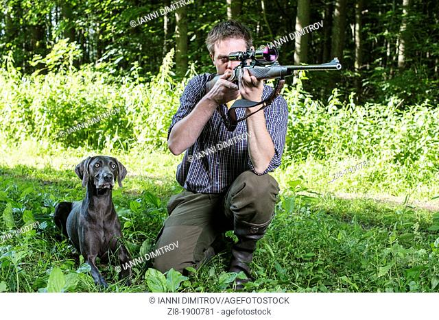 Hunter with dog,aiming with rifle with telescopic sight