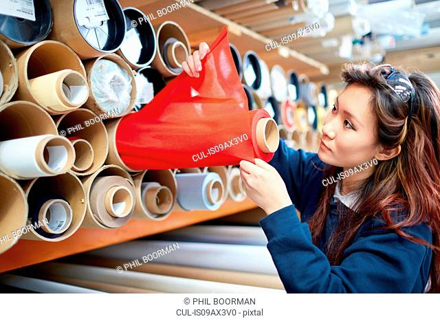 Female worker examining red fabric for roller blind in factory