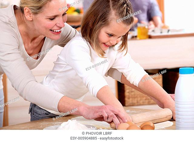 A mother teaching her daughter how to bake