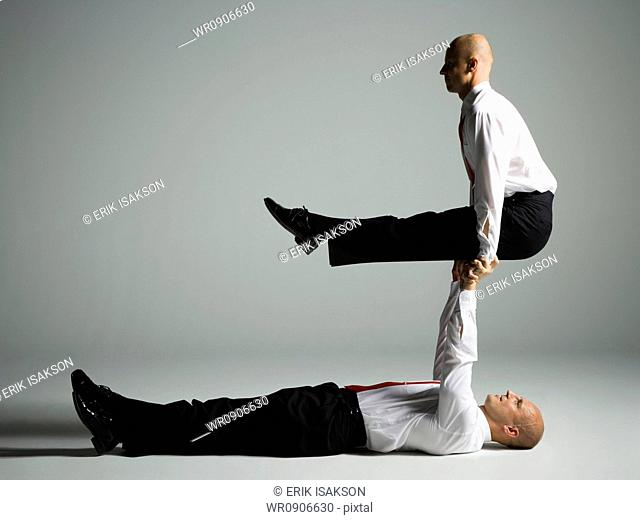 Profile of two male acrobats in business suits performing