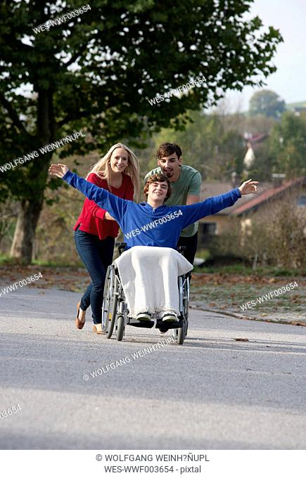 Young couple with friend sitting in wheelchair
