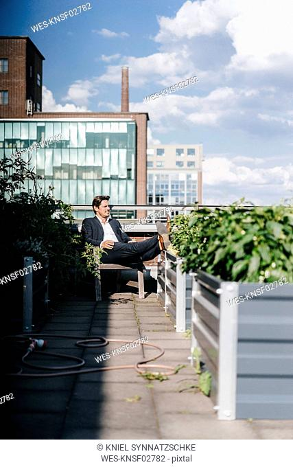 Businessman relaxing in his urban rooftop garden