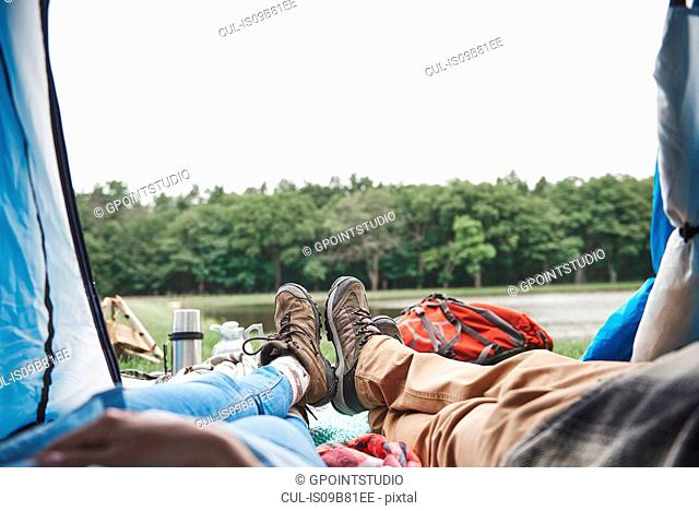 Mature couple relaxing in tent, looking out at view, low section
