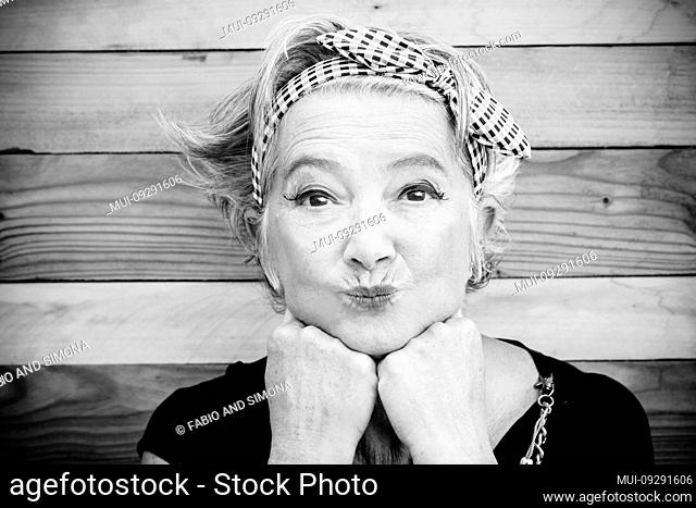 senior and mature woman with makeup is looking at the camera - funny moment with a wood table at the background - cheerful old lady go crazy and nice looking at...