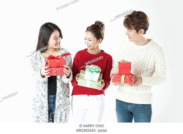 Three young smiling people holding present boxes