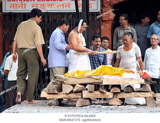 NEPAL Pashupatinath, cerimonia induista di cremazione sulla riva del sacro fiume Bagmati . Il corpo del defunto posa sulla pira di legna