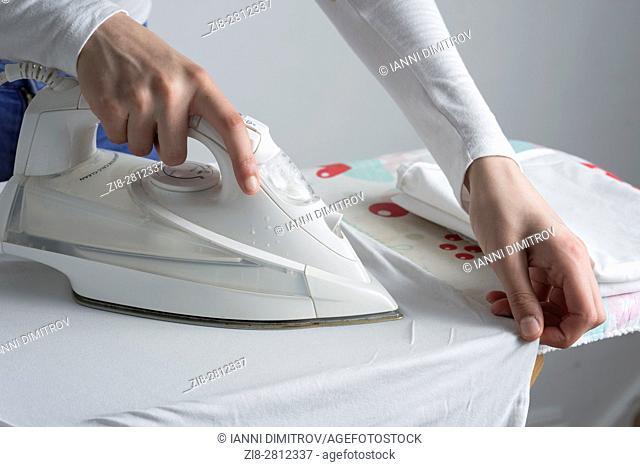 UK,Teenage girl irons her uniform-close-up