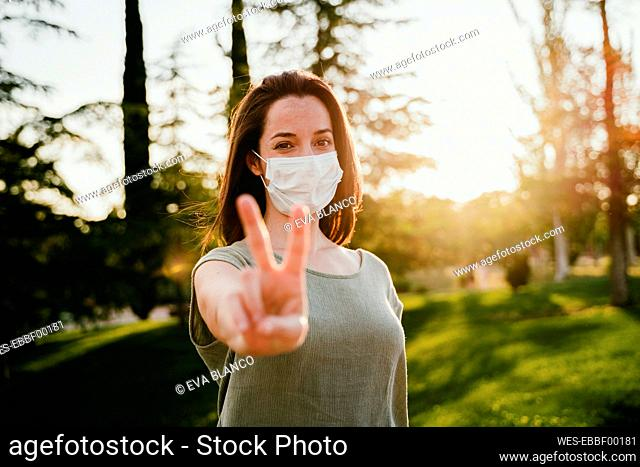 Portrait of woman wearing protective mask in nature showing victory sign