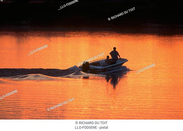 Fishing Boat on Move with Men Silhoetted in the Morning Light  Chobe River, Namibia, Africa