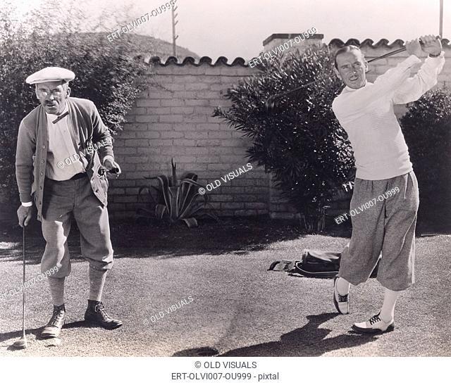 Men playing golf in backyard (OLVI007-OU999-F)