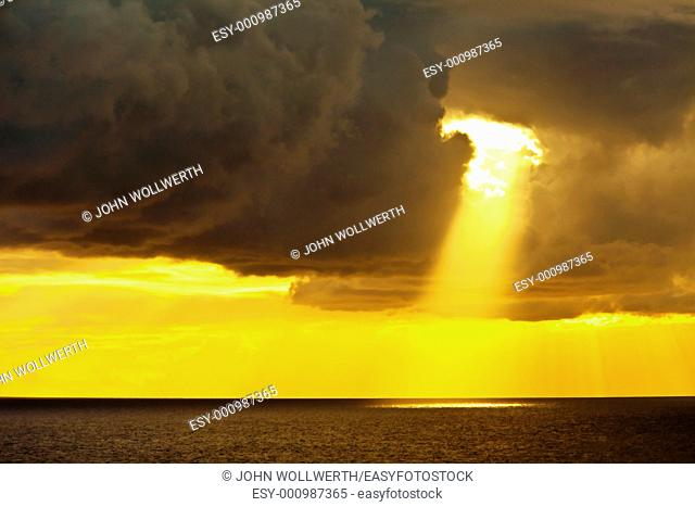 single sunbeam shining through dark clouds on the caribbean sea