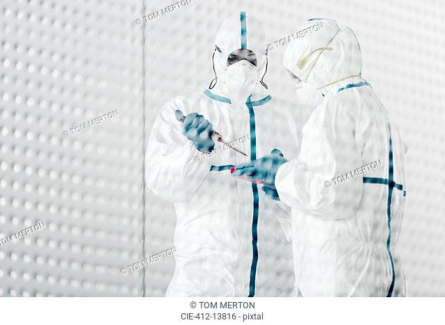 Scientists in clean suits working in laboratory