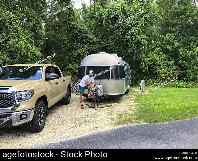 Man standing by pickup truck and trailer in camping park, Ocala Florida, USA