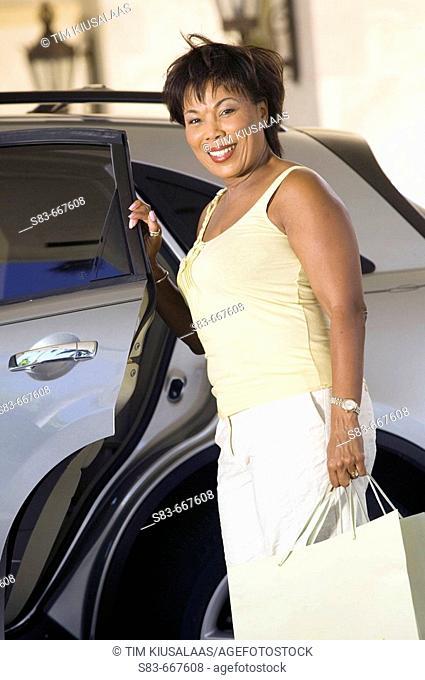 Senior woman unloading bags from car