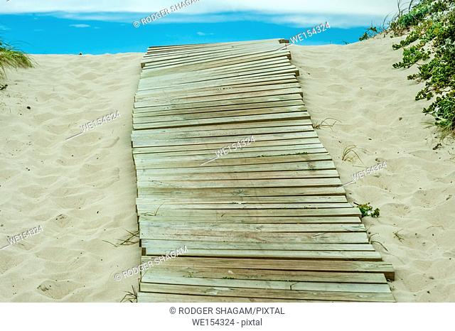Boardwalk to the beach over a coastal dume. the walkway helps protect the dune from eroding. Cape Town, South Africa. On the Table Bay coastline