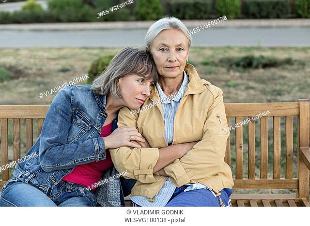 Portrait of senior woman sitting on a bench with her adult daughter