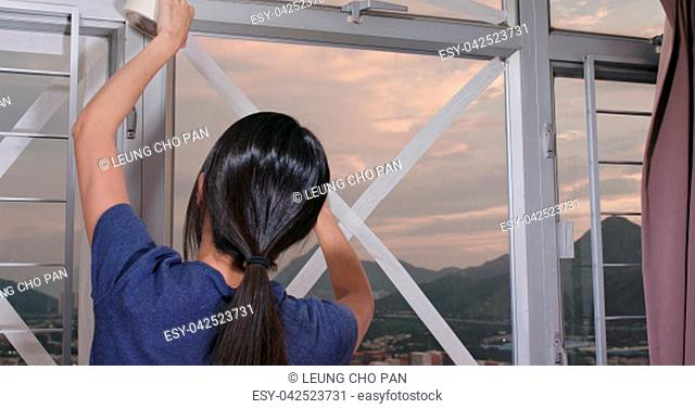 Woman stick tape on window at home to prevent typhoon