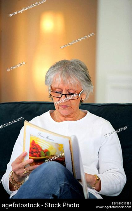 Portrait of a senior woman sitting on a sofa reading a magazine