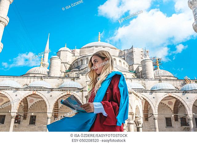Attractive beautiful girl with covered clothes looks Turkish map with view of Sultan Ahmet Mosque on background in Istanbul,Turkey. Travel Concept