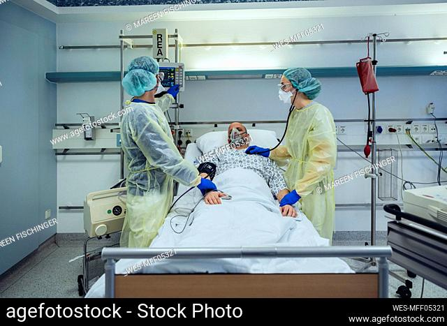 Doctors caring for patient in emergency care unit of a hospital looking at screen
