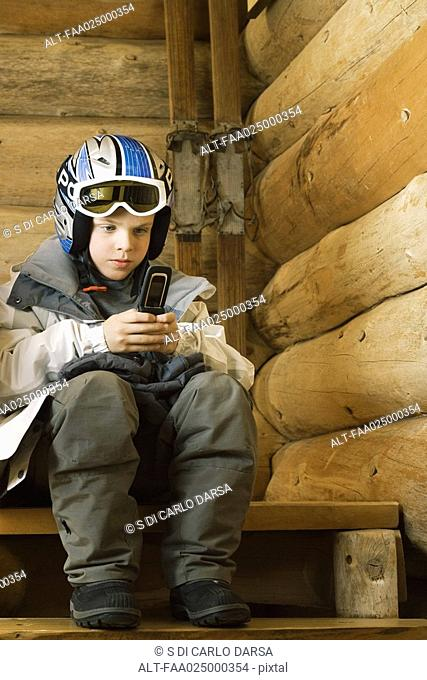 Boy in ski gear sitting, using cell phone