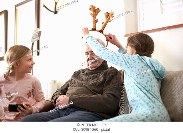 Sisters putting reindeer antlers on sleeping grandfather